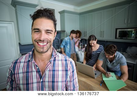 Close-up portrait of cheerful man with friends in background at home