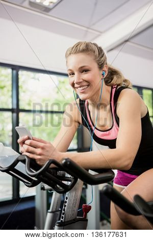 Portrait of woman sitting on exercise bike and listening music on smartphone