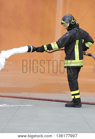 Fireman With An Extinguisher With Foam Under The Orange Smoke