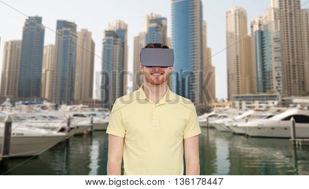 3d technology, virtual reality, travel, entertainment and people concept - happy young man with virtual reality headset or 3d glasses over dubai city street background