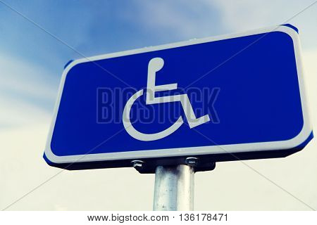 traffic laws and highway code concept - close up of road sign for disabled outdoors