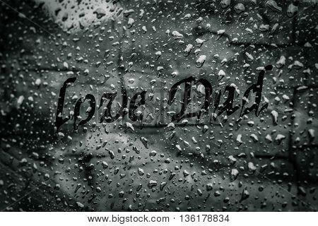 Love dad text on water drops on glass window in raining Season