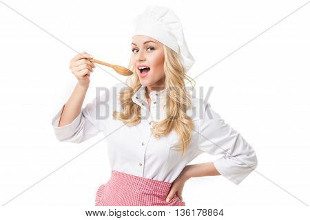 Portrait of young blonde woman in uniform tasting food from spoon.Studio shot.Isolated.