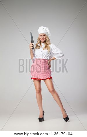 Portrait of smiling blonde woman in chef uniform holding knife.Studio shot.