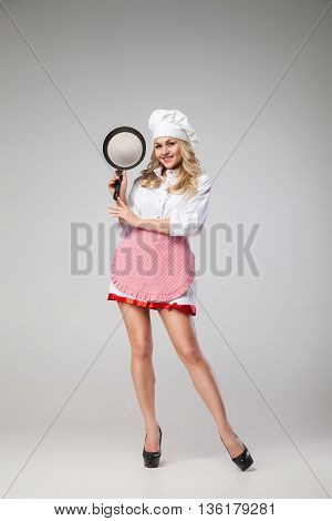 Portrait of beautiful young woman in apron and hat with frying pan looking at camera.Studio shot.