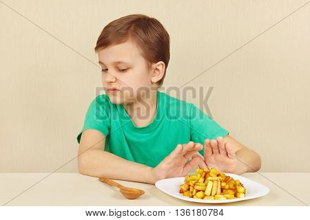 Little cute boy refuses to eat a french fries