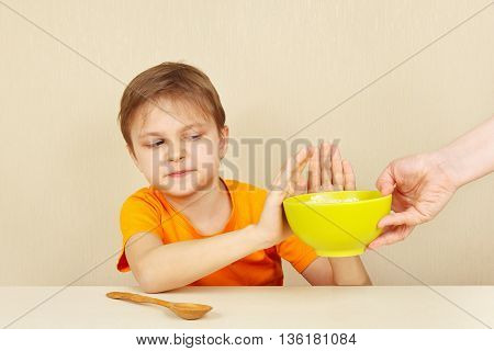 Little unhappy boy refuses to eat a porridge