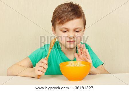 Little displeased boy refuses to eat a porridge