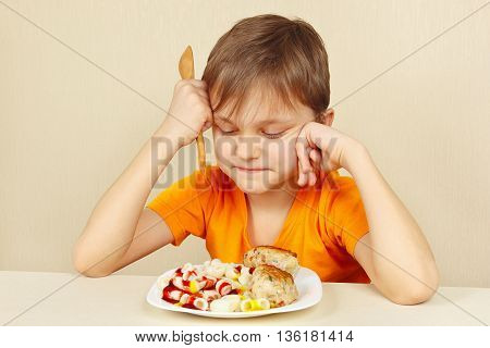 Little disaffected boy does not want to eat a pasta with rissole