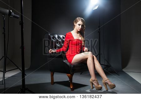 Portrait of beautiful brunette on black leather chair in red dress