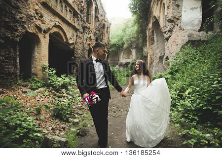 Happy newlyweds near the ancient castle on the walk.