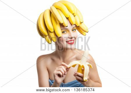 Beautiful woman with make-up and bananas on head peeling banana.Studio shot