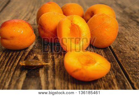Fresh apricot with water drops on wood table