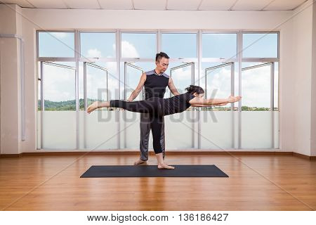 Yoga Instructor Correcting Student Performing Warrior 3 Or Virabhadrasana 3