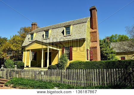 Raleigh North Carolina - April 18 2016: 1779 wooden clapboard Joel Lane House Museum with gambrel roof portico dormers and brick chimneys