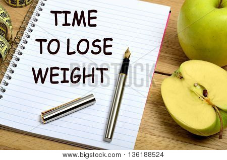 The words Time to lose weight on notebook