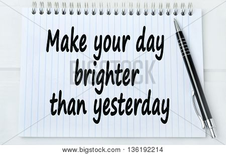 Text Make your day brighter than yesterday on notebook
