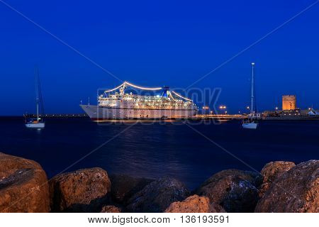 cruise ship at the port between two sailing yachts dusk