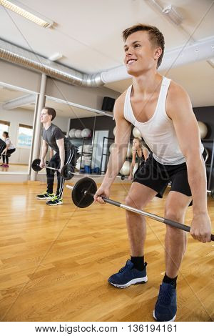Man In Sportswear Lifting Barbell In Gym