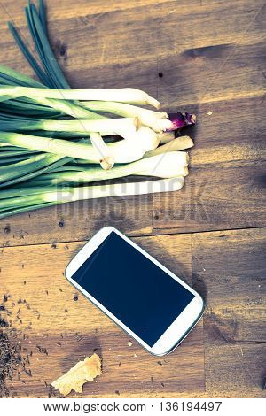 A smartphone lying in a natural kitchen with white bread, spices, olives and spring onions.