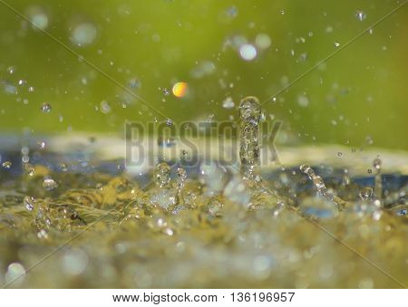 Heavy rain splashes into water creating rebounding water droplets