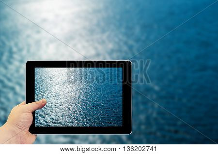 Tablet Photography Concept. Taking Pictures On A Tablet. Blue Water With Sun Reflections