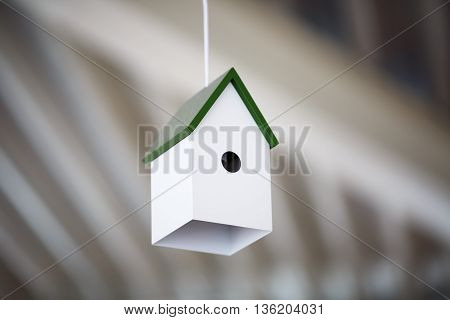 Chandelier birdhouse. Lamp in the form of a white birdhouse with a green roof. Shallow depth of field. Selective focus.