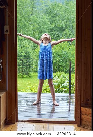 Schoolgirl  standing barefeet on the porch enjoying warm summer rain