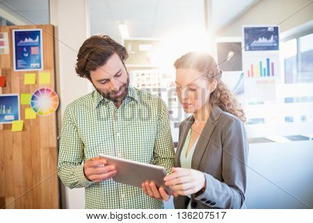 Businessman and businesswoman discuss using tablet in office