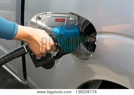 Men hold Fuel nozzle to add fuel in car at gas station