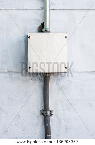 Electrical control box on the cement wall of the factory.