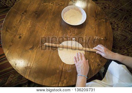 A woman preparing a Tatar pie on a table.