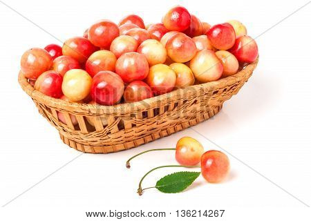 yellow cherries in a wicker basket isolated on white background.