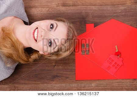 Building ownership property real estate security access concept. Young lady on floor with home. Girl lying next to house cutout keyring.