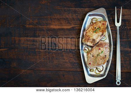 Roasted meat on a metal plate and fork. Top view with copy space.