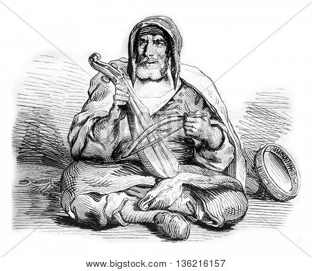 Jewish musician, costume Mogador in Morocco, vintage engraved illustration. Magasin Pittoresque 1842.