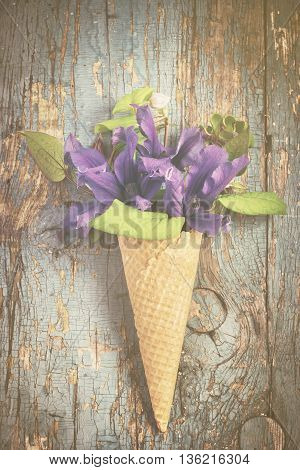 Summer garden flowers in ice cream waffle cone on vintage background. Gardening concept