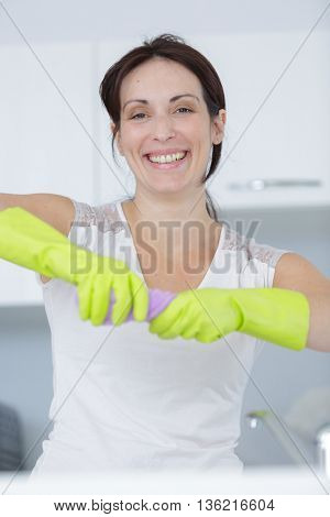 beautiful happy young housewife wearing gloves and holding a detergent