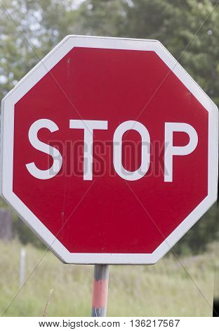 a red and white  stop sign for traffic