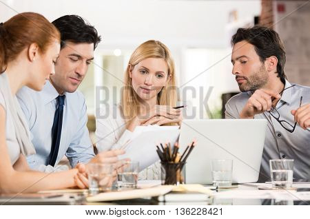 Manager with his colleague discuss about the business plan. Business team working at office. Business meeting in a conference room analyzing corporate reports.
