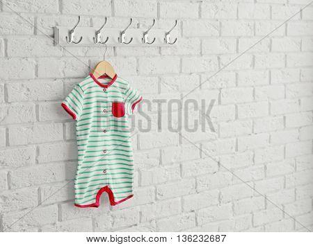 Bright striped romper on brick wall