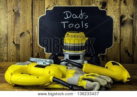 electric power tools and work gloves in front of chalkboard reading dads tools with house fly on router