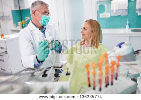 Male dentist discusses about upcoming intervention with female patient