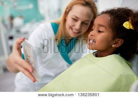 Sweet black girl patient showing in mirror her teeth to dental assistant in dental clinic
