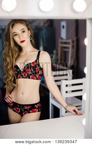 Young beautiful woman ooking in a mirror  at dressing room with vintage mirror dark room