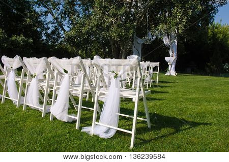 Arch for wedding ceremony. White decorated chairs on a green lawn. Chairs set in rows for the wedding ceremony. They are decorated for the festive event. Chairs are on the green lawn outside.