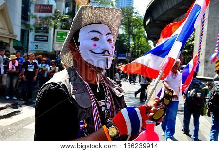 Bangkok Thailand - January 13 2014: Man wearing white face mask carrying the Thai flag at Operation Shut Down Bangkok protest *