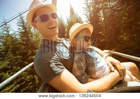 Father and little son using lift chair on the summer resort in Bulgaria