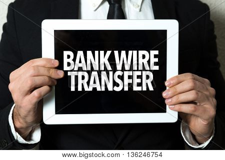 Business man holding a tablet with the text: Bank Wire Transfer