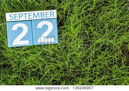 September 22nd. Image of september 22 wooden color calendar on green grass lawn background. Autumn day. Empty space for text.